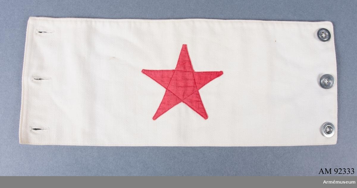 """Armbindel tillverkad av vitt tyg med en applicerad röd stjärna. Märkt på baksidan med """"Irma Fraenckel""""."""