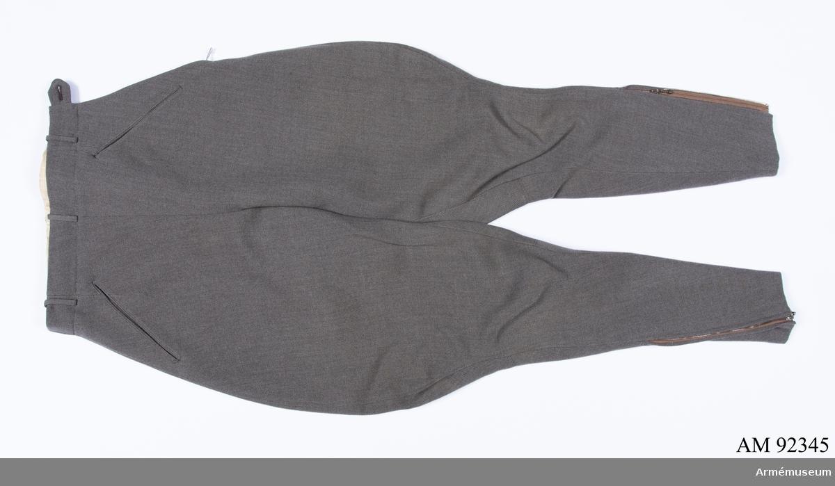 Ridbyxor sydda i grå yllediagonal med dragkedjor i benen.