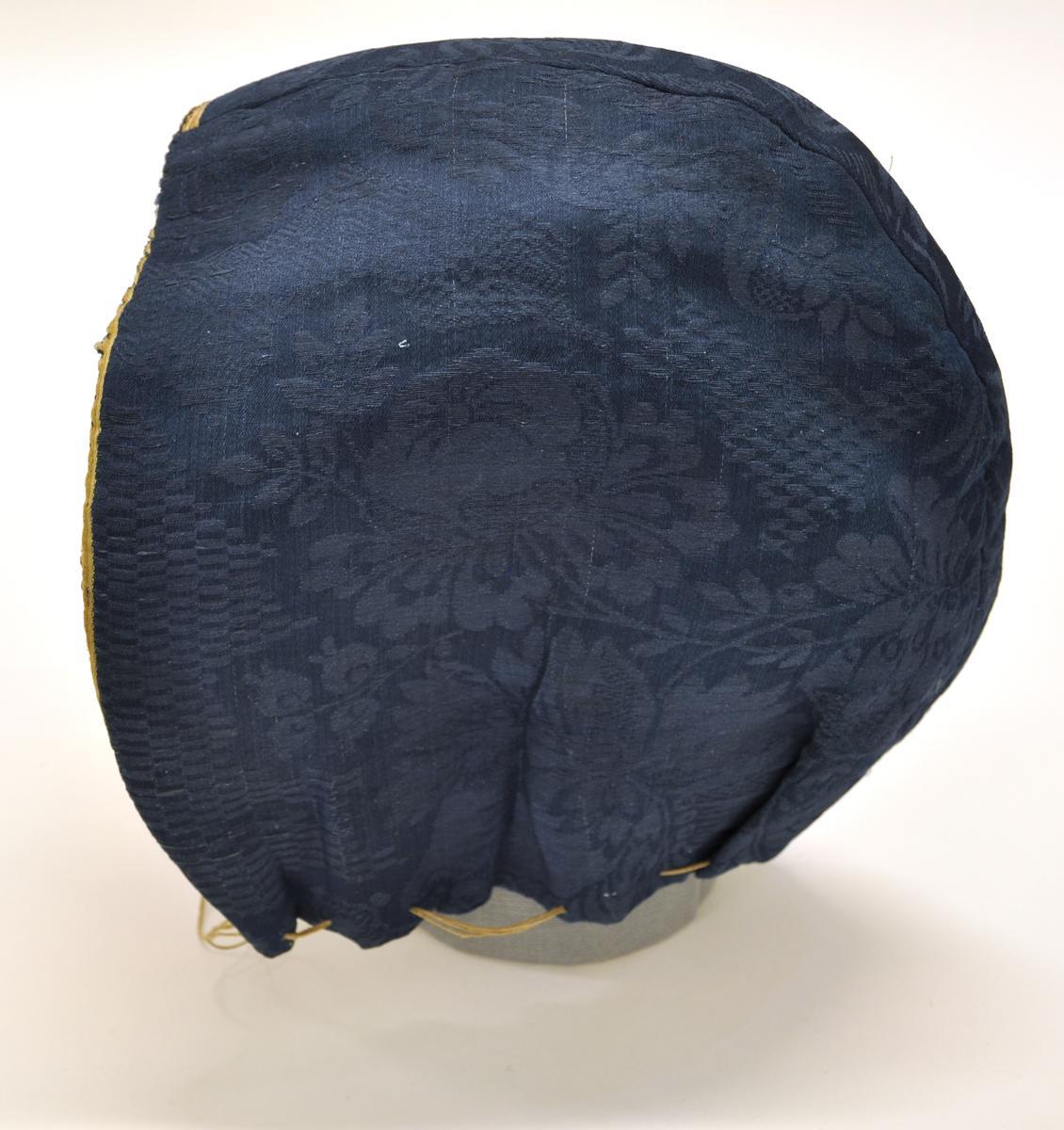 Mjuk bindmössa från Björketorps sn, Bollebygd hd. Blå sidendamast med blommig mönster. Fodrad med ofärgat linnetyg. Snöre som rynkar nederkanten.