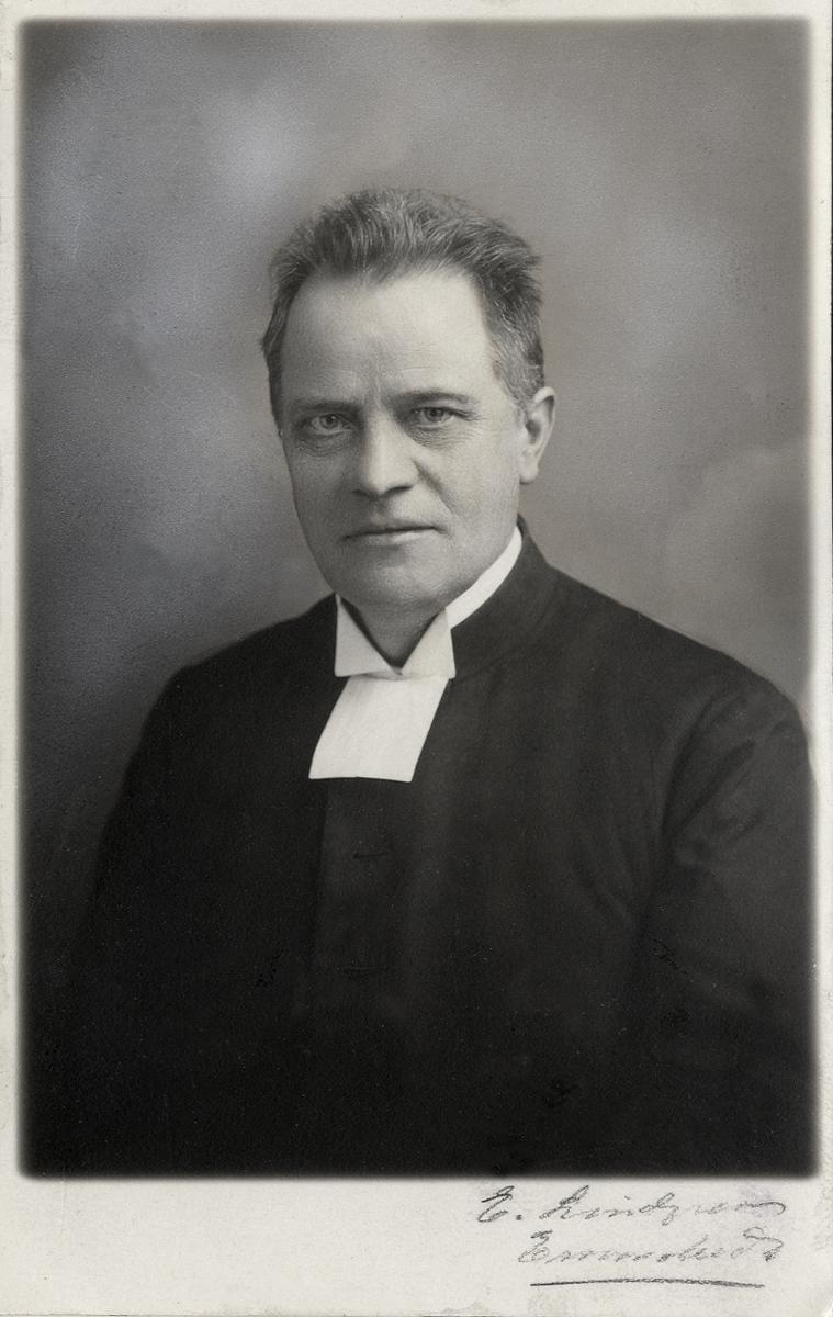 Porträttfoto av en man i prästrock med prästkrage.  Midjebild, halvprofil. Ateljéfoto.