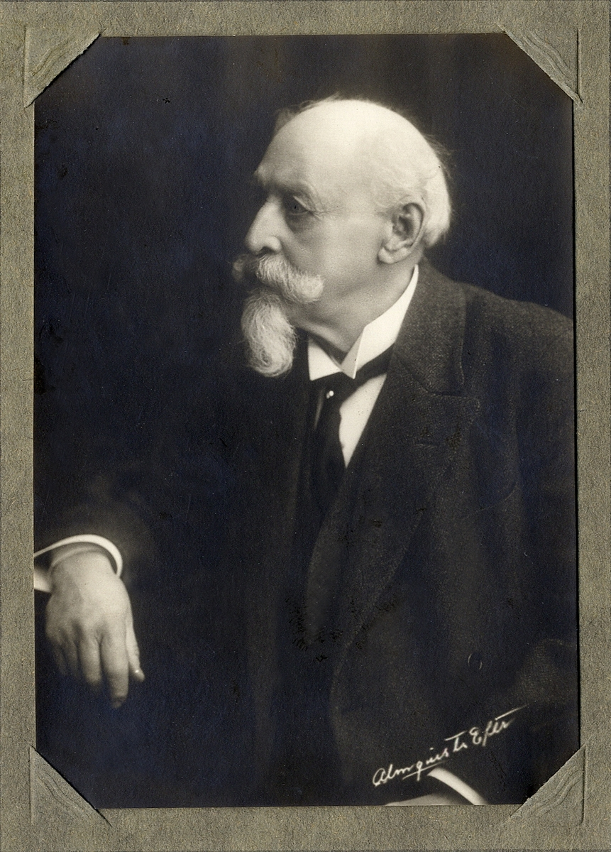 Porträttfoto av en äldre man med pipskägg, klädd i mörk kavajkostym med stärkkrage och slips. I slipsen skymtar en kråsnål.  Midjebild, halvprofil. Ateljéfoto.