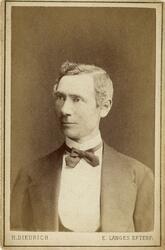 Porträttfoto av en medelålders man i kavajkostym med väst, s