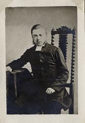 Porträttfoto av en man i prästrock med prästkrage. Han sitte