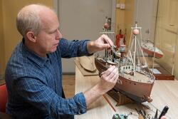 Modellbyggare Stefan Bruhn med en modell av fyrskeppet Grund