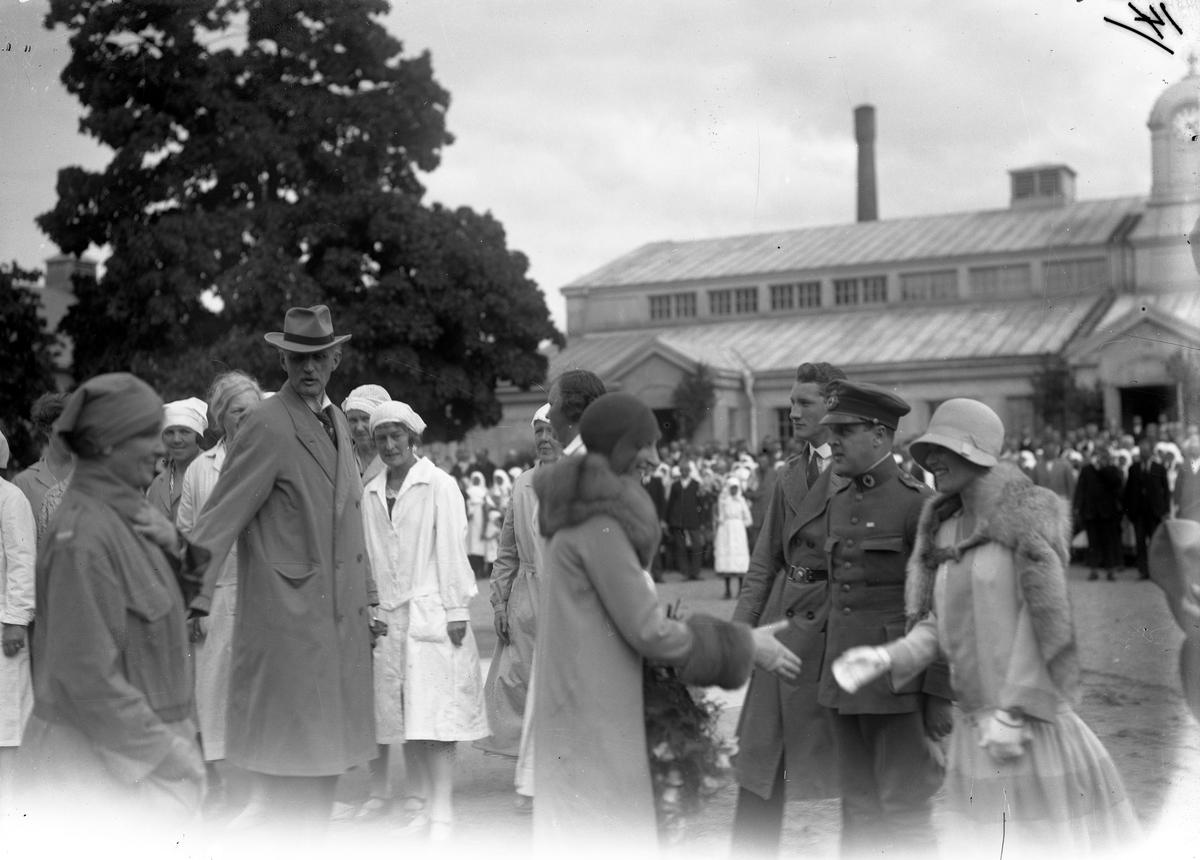 Svenskbyborna när de kom till I:12s före detta kaserner på Ryhov i Jönköping 1929. Prins Carl i hatt till vänster och prinsessan Ingeborg framför.