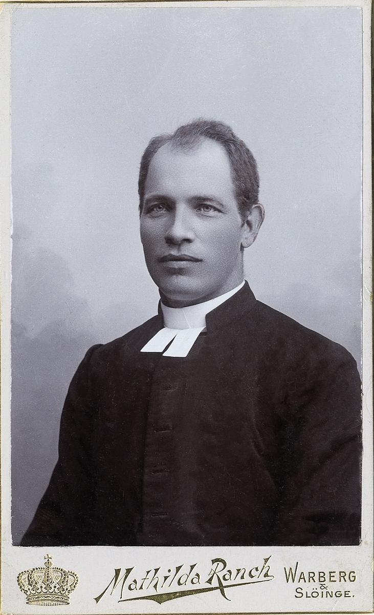 Foto av en man i prästrock med prästkrage m.m. Bröstbild, halvprofil. Ateljéfoto.