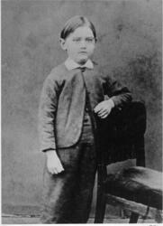 En liten pojk, A E Bolling, i helfigur. Han är klädd i småru