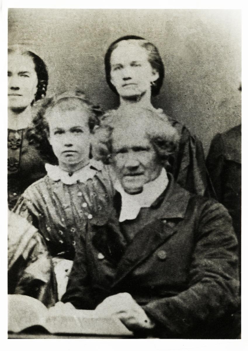 Foto av en äldre man med polisonger, klädd i rock, prästkrage m.m, omgiven av sina barn.  Bröstbild, halvprofil, Ateljéfoto.