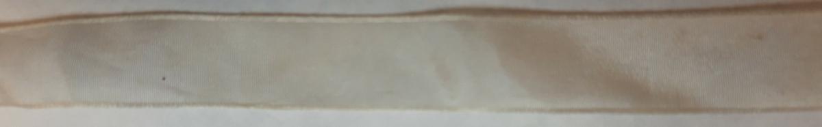 Metallkrone med fem spir. Påsydd valknederst, Brodert bånd og metallknipling rundt valken. Krona er pyntet med metallheng og glassperler. Bak på det broderte båndet rundt valken er det festet bånd. Midt bak et bredt bånd i rødt med metallkniplinger. På hver side av det brede bånd med lys bunn under metallkniplinger med rød kan vendt ut fra det røde midtbåndet. Deretter fire smalere bånd på hver side av disse. Dosse er festet samlet med en liten sløyfe på det bredeste der det er festet på valken.  En plastkam er påsydd valken sammen med to hvite, nyere bånd. Antagelig gjort i nyere tid for å feste krona og knyte under haka.