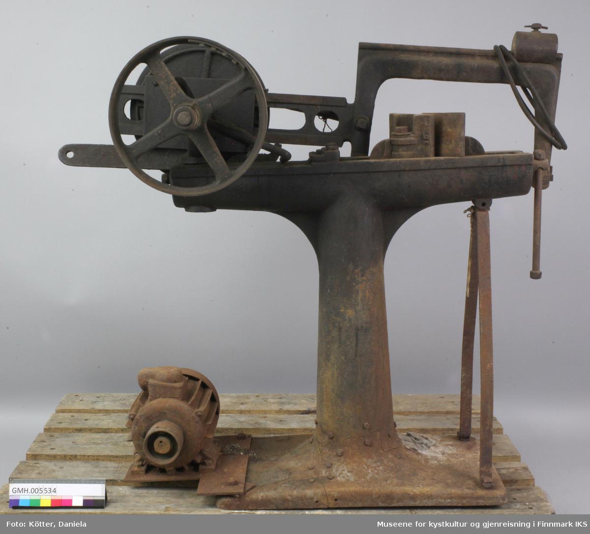 Gjæringssaga er laget av støpejern og bærer preg av lang og intens bruk. Søyla har en skade ved foten som ble reparert. Saga drives elektrisk. Ved foten er det en motor som driver et reim. Strømkabelen og reim mangler. Maskinen er oppbygd t-formet. Reima fra motoren føres over et hjul på ene enden av T'en. Dette hjulet er forbundet med en arm som i enden har en festeanordning for et sagblad som beveges frem og tilbake når hjulet roterer. På motstående side av T'en er det en festeanordning for emnet som skal sages. Her kan vinkelen justeres.