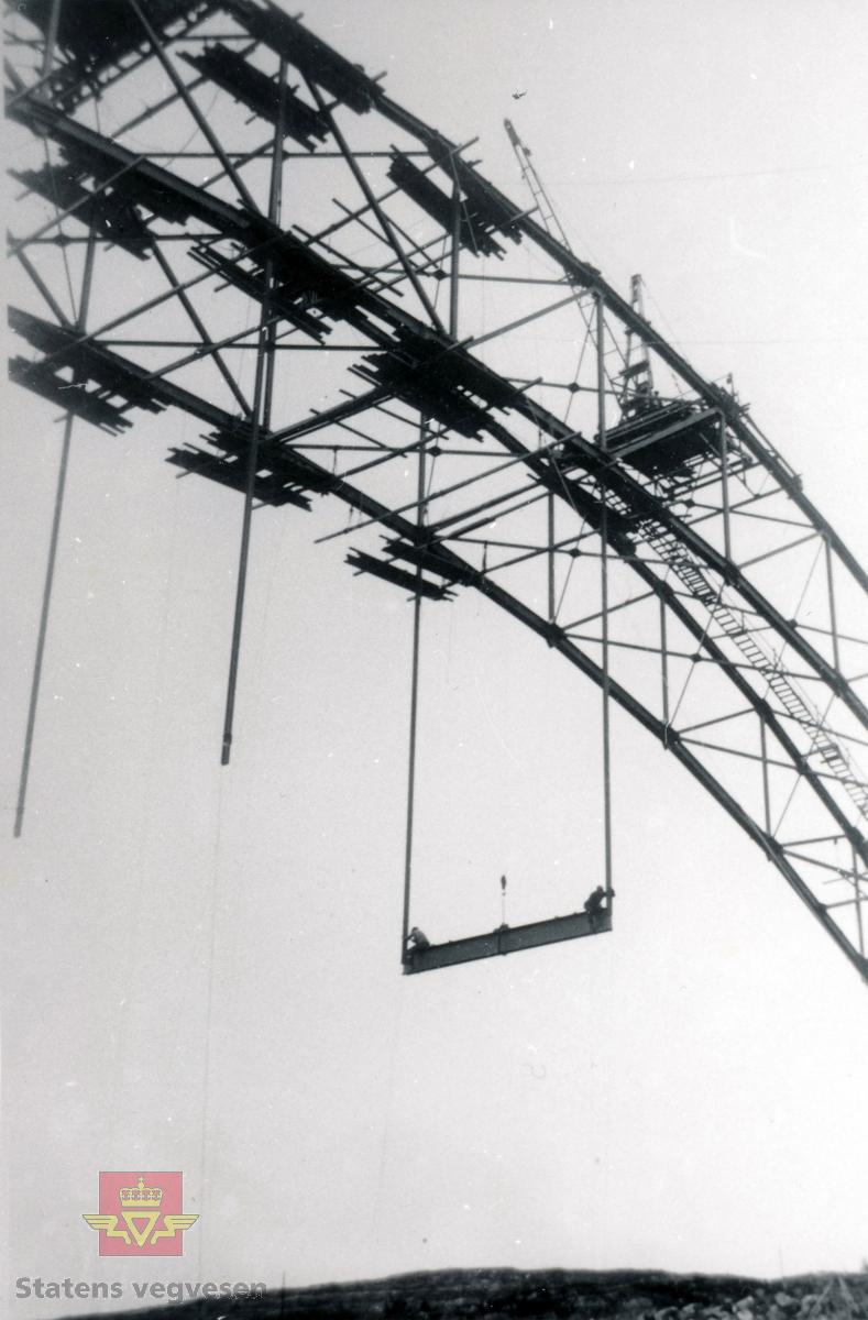 """Gamle Omsund bru som går fra Nordlandet i Kristiansund til Rensvikholmen. Brua ble bygd i 1939 og tatt i bruk i april 1940, samtidig som Rensviksundbrua fra Rensvikholmen til Frei stod ferdig..  Bak på foto står bl.a.: """"Omsund bru under bygging. De må tåle å arbeide i høyden disse to karene. Vegbanen skal gå over den bjelken de sitter på."""""""