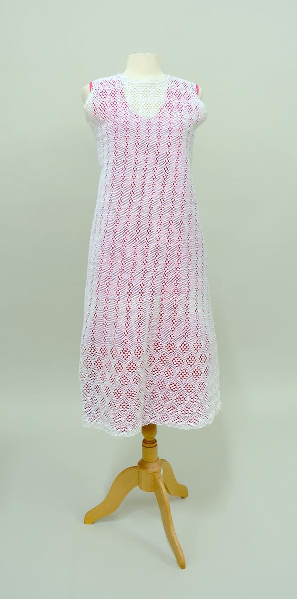 Kjole i tre deler: Kjole:TGM-BM.2000:083.A  Underkjole: TGM-BM.2000:083.B  Jakke:TGM-BM.2000:083.C Kjolen har rund hals og ingen armer. Åpen jakke med lange ermer. Både kjole og jakke er utført  i telemarksbinding. Underkjolen er rosa og er laget av silke.