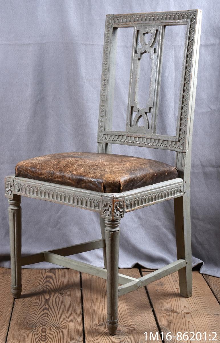 Gustavianska stol med svarvade framben med hörnfleuron och kanelyrer, raka bakben sarg och rygg med så kallad nagelskärning. Genombruten rygg med horisontel bricka så kallad Gunnebobricka, stoppad lös sits, klädd med oxhud.   Neg.nr: 81/1043:2