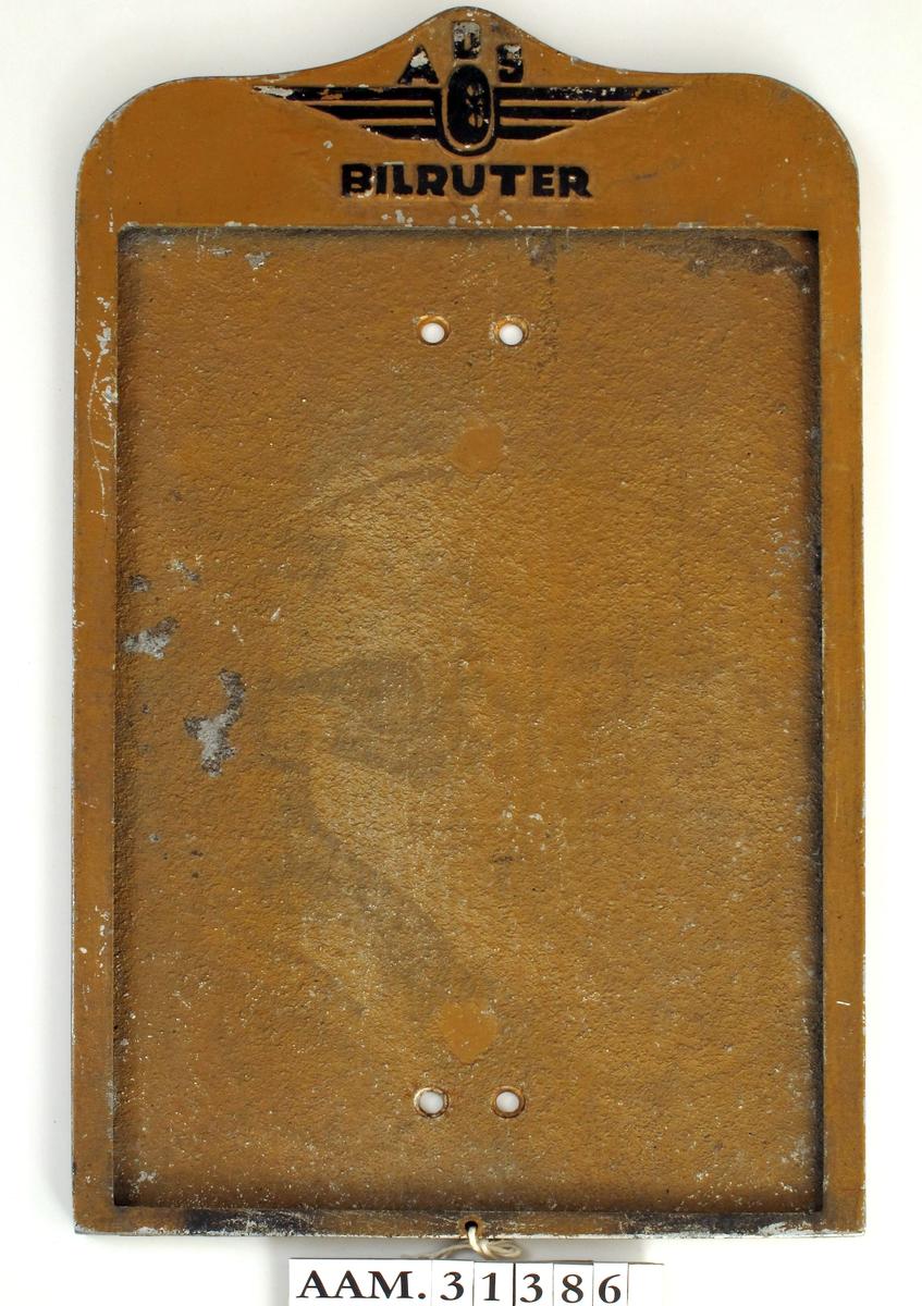 En ramme av metall, uten glass eller plast foran, med spalte under for å  sette på plass ark med rutetider. I bakplaten 2 x 2 hull til skruer, for å feste holderen til stolpe, vegg e.l.