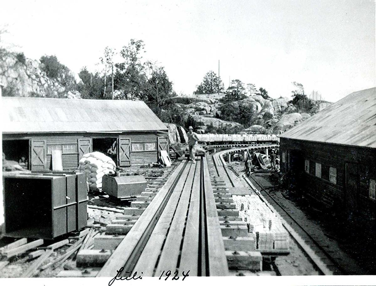 """""""1924"""" Nitriden. Skinnegang for intern transport. Til venstre dieseldrevet lokomotiv med opplastet tralle med sekker med bauxitt. I bakgrunnen støpte aluminiumbarrer. Til høyre for skinnegangen aluminium ignots. Bygningen til høyre er lager for ferdigprodukter. En mann kommer trekkende med en tralle."""