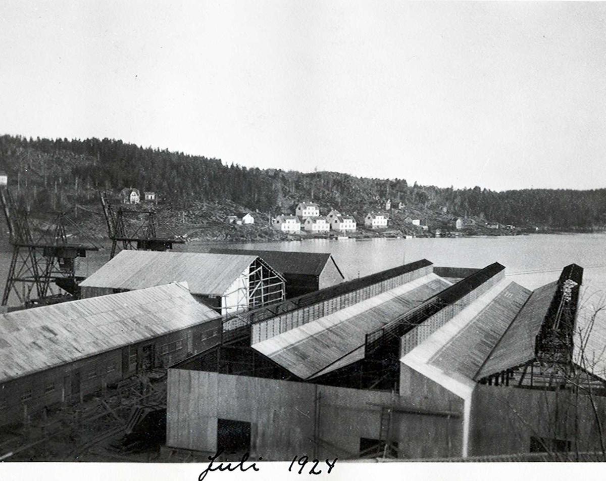 """""""xx/07-1924"""" Nitriden. Tre stekeribygninger til høyre. Til venstre lagerbygning for ferdigprodukter, og mottak/lager for bauxitt. Kraner helt til venstre. Nitridens boliger på Omdalsøyren, Tromøy, i bakgrunnen. Tromøysund."""