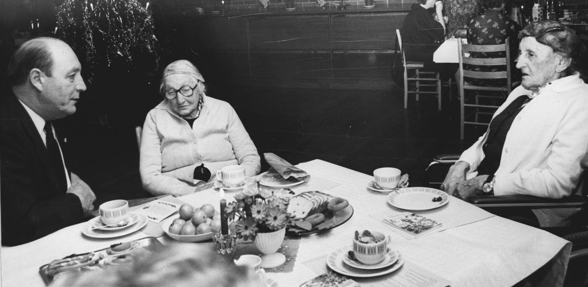 Ordfører Rønold Haugen ved kaffebordet med to eldre kvinner.