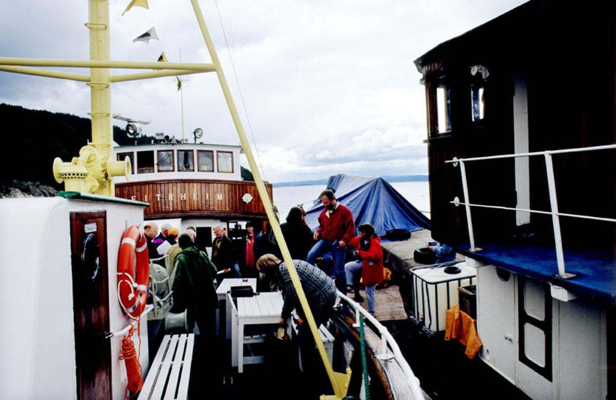 Oslofjorden. Båt/fiskeskøyte ligger ved kai: Eitrheim. Mennesker på vei til å gå om bord.