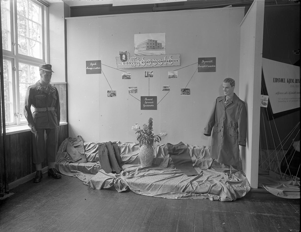 Fra Eidsvoll Bygdeutstilling i 1955. Stand for Eidsvoll Konfeksjonsfabrikk – som har sysal, presseri, skjæreri og knapphullmaskin.