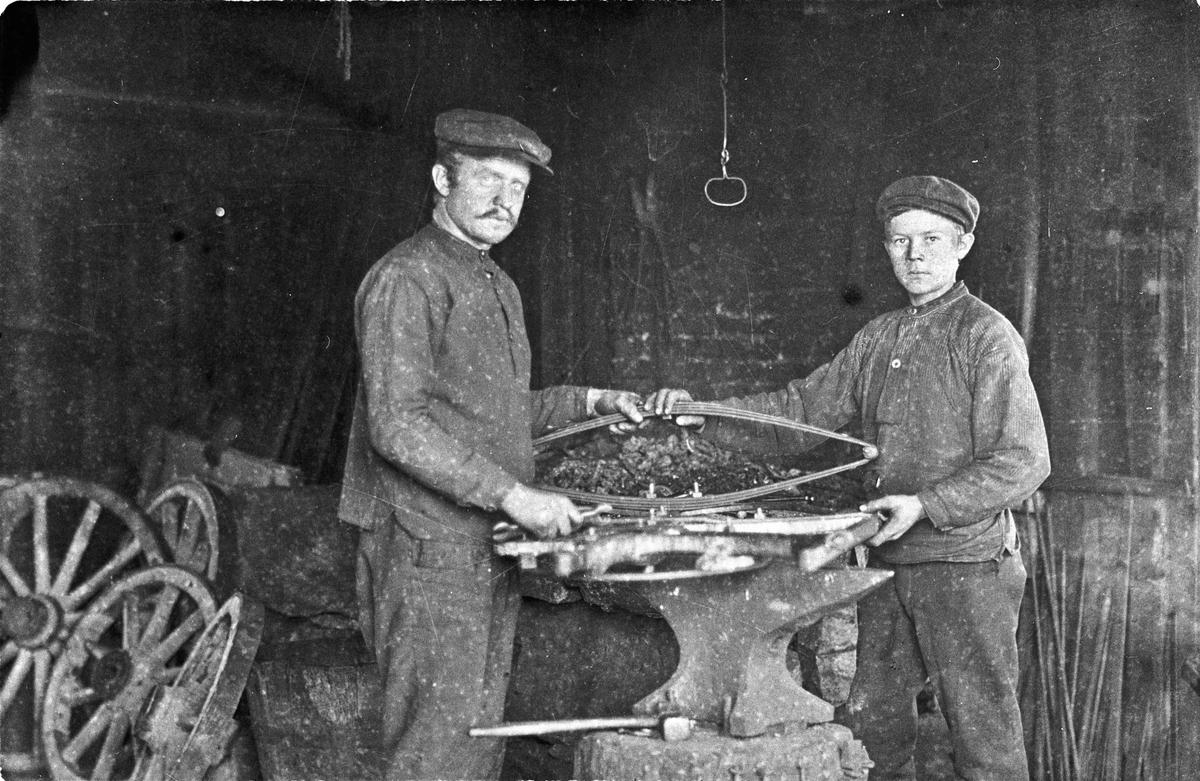 I smia. Arbeid med fjæring til hestevogn. Andreas Klaseie og Karl Bredesen.