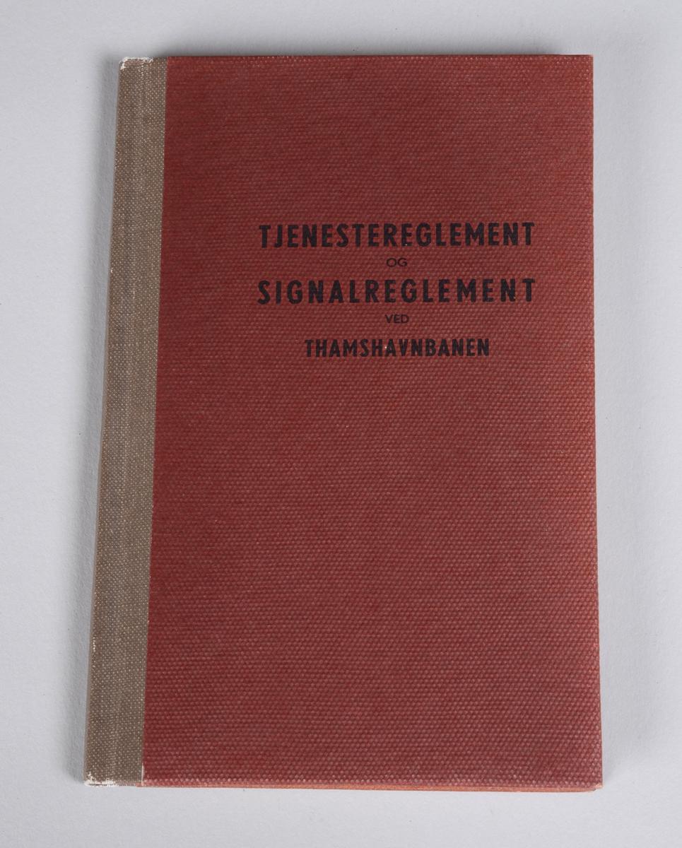 Rektangulær bok med stivt rødt omslag, beige rygg og svart skrift. Omhandler reglement ved Thamshavnbanen.