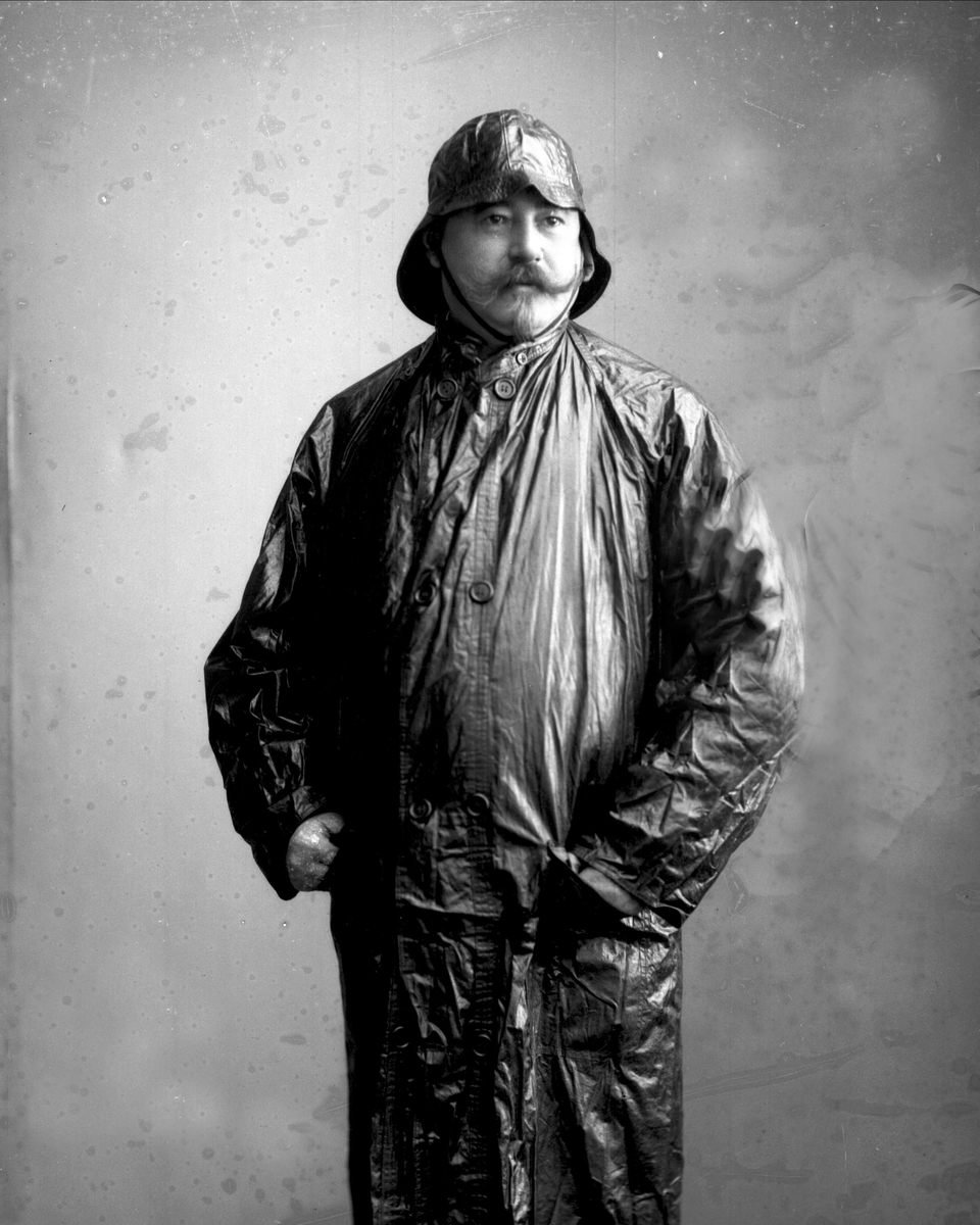 Portrett, mann i regntøy. A. Sand.