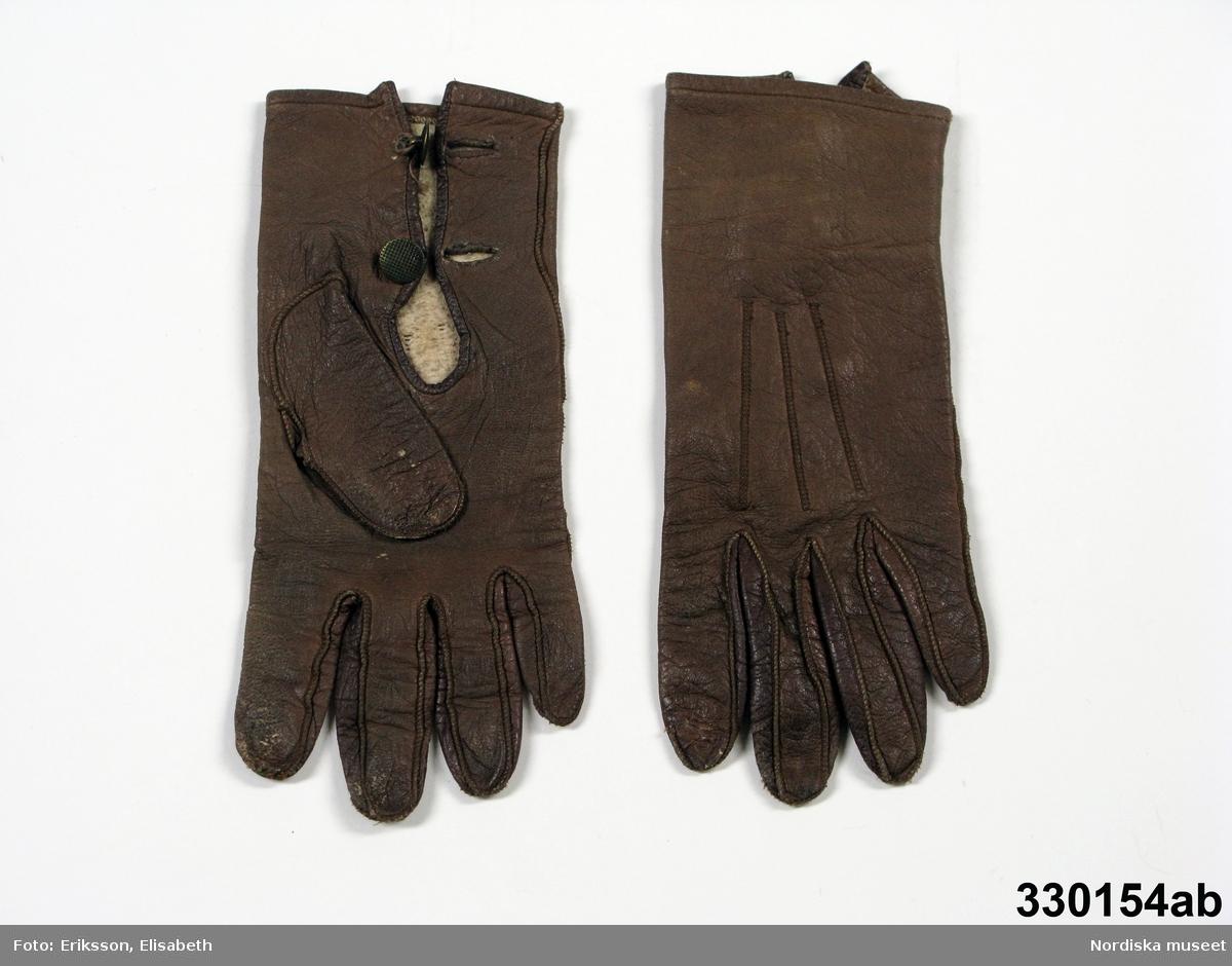 """Ett par barnhandskar [a-b], fingerhandskar av brunt skinn, maskinsydda med utåtliggande sömmar och tre sömmar på ovansidan. Sprund knäppt med 2 små räfflade mässingsknappar och knapphål. Ofodrade. Väl använda. Ser ut att passa en hand på en flicka ca 4-7 år. Förvarades i liten pappask inv.nr. NM.0330155+ med skriven text i locket: """"Margit von Heijnes första handskar..."""" Har tillhört Margit von Heijne född 1898 på Lillienäs herrgård i  Småland vid sjön Bolmens norra ände."""