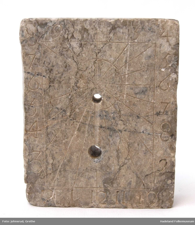 Rektangulær, flat kleberstein med innrissede tall i kanten og en sol i midten hvorfra det går streker ut til hvert av tallene.  Trekantet viser mangler. Trolig vært i messing.