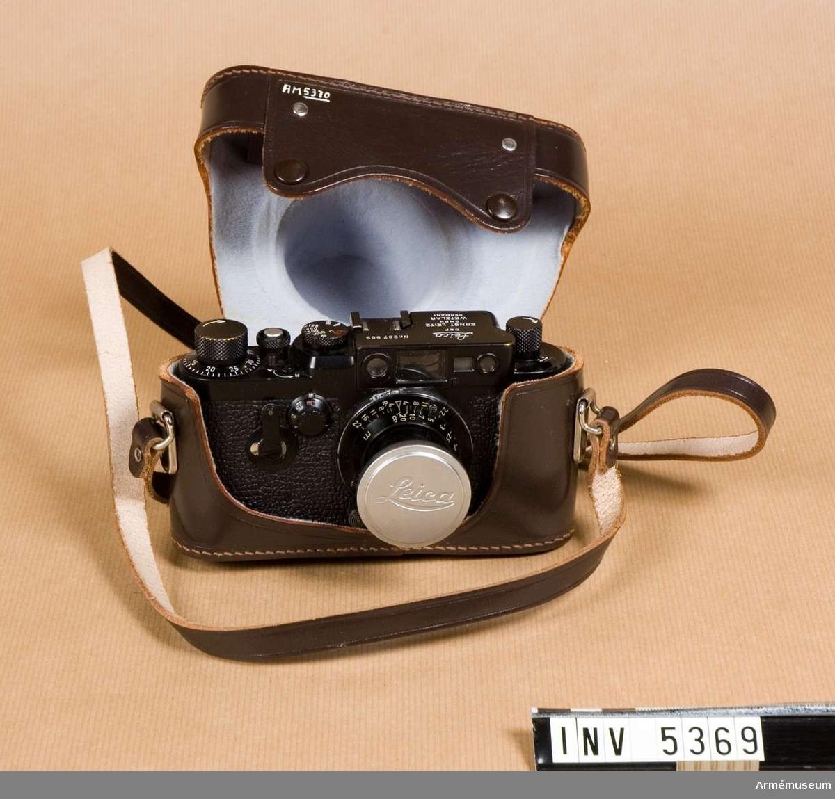 Kamera 151, Leica. M3830-151A0.Tillverkningsnummer 987969, objektiv 1427002.  Kameran är svart med vit och röd text. Den är försedd med rem. Objektiv svart med vit text. Objektivets mått är 50 x 50 mm. Kameran är försedd  med blixtsynkronisering.   Objektiv är Elmar f=50 mm 1:3,5. Det är  inskjutbart och har ljust lock.   Kameran är märkt med emblemet  tre kronor och objektivet är svart vilket gör dem eftertraktade  bland samlare. I kameran finns en leicakassett och i  stativgängan en adapter för den mindre stativskruven, 1/4 tum.  Kassettspolen är svart.  Kameran i gott skick, objektivet likaså men saknar låsskruven för avståndsinställningen. Slutaren fungerar. Slutartider  1-1000/sek, T och B; tiderna är fördelade på två skalor.  Bländarvärden 3,5-22.  1992-02-27 packad i låda / Erik Walberg.