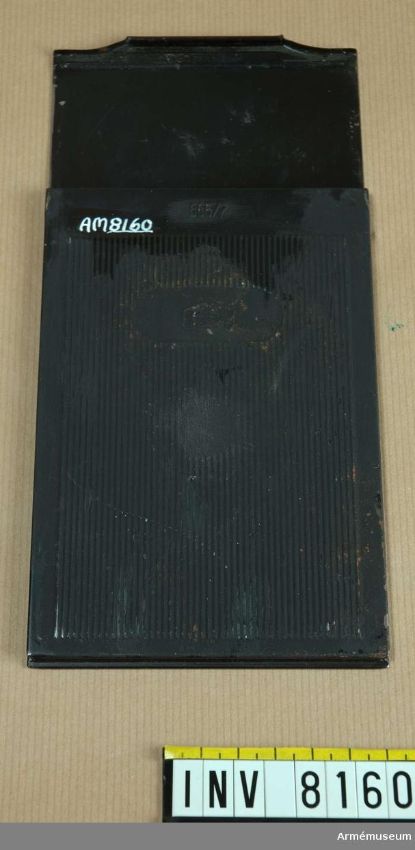 """Samhörande nr är AM 8151 - 8199.Kassett. För fotografiskt bruk.Kassetten är tillverkad av svart korrugerad plåt med utdragbar skiva (för glasplåt?) eller den utdragbara skivan utgör baksida. Slät, svart i greppet.Märkt ZEISS IKON 665/7 Made in Germany.Till storbildskamera 1 Brückner resekamera. Ur fotomaterielsats 7. I väska """"unika"""" AM."""
