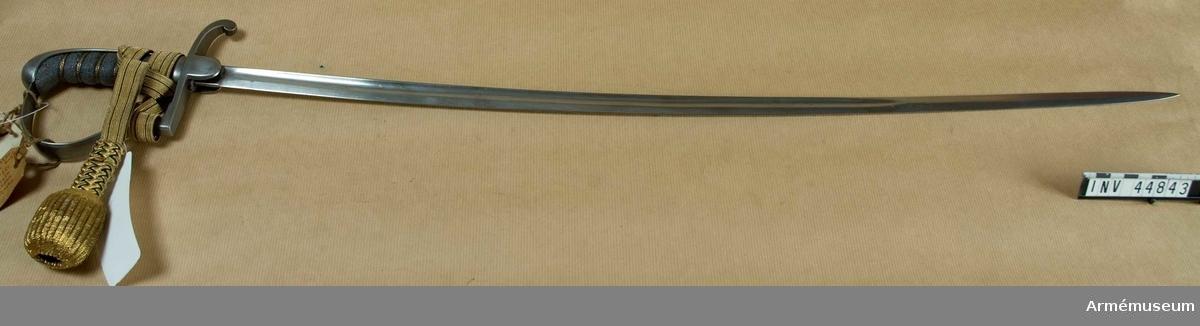 Grupp D II Klingan är svagt böjd, skålslipad och till sin största del  eneggad. Saknar gravyr, märken och stämplar. Fästet är av järn.  Kaveln är klädd med fiskskinn, har 6 ränder i vilken en lindning  bestående av 2 enkla och en spunnen tråd äro virade.