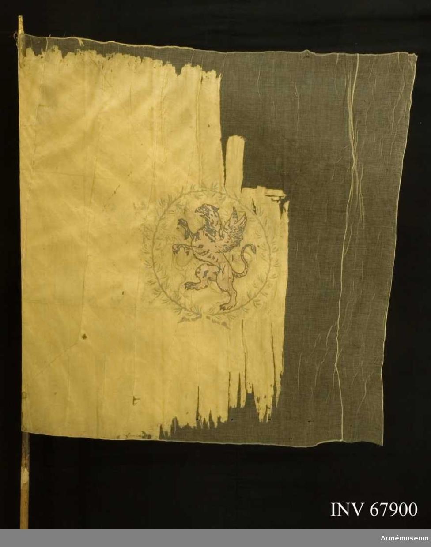 Duk: Tillverkad av enkel gul sidenkypert. Sydd av tre horisontella våder.  Dekor: Broderad lika på båda sidor, i mitten Södermanlands sköldemärke, en grip i svart applicerat siden omgivet av en liten krans, av två upptill och nedtill hopknutna lagerkvistar, nedtill med långa gula band, stjälkar i brunt, blad i grönt och bär i gult silke.  Kantad med ett brett gult sidenband och förgyllda spikar. Saknar holk och spets.  Märkt: Läsbar etikett på stången.