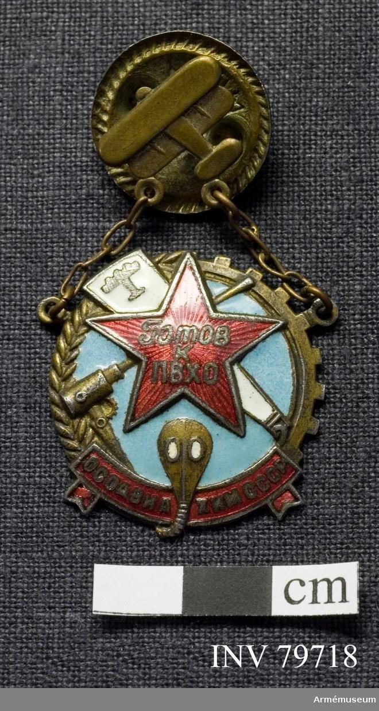 """Grupp M.  För kriget Finland-Ryssland 1940. Åtsidan: En liten modell av ett flygplan av gul metall, från vilken nedhänga två kopparkedjor (den ena avsliten), uppbärande dekorationen, som består av en metallkantad, femuddig stjärna av röd emalj, med inskriften: (kyrilliska bokstäver) ("""" oviatik och kemi"""").  Stjärnan vilar på i kors lagda en handgranat och en miniatyrflygplans- vinge samt två andra föremål, allt lagt på en cirkelrund, ljusblå botten.  Denna omgives i sin tur av en cirkelrund kopparanordning, bestående till ungefär en tredjedel av taggar, till ungefär en tredjedel av ett flätat rep (?) och till sista tredjedelen av ett metalskott rött emaljfält med två nedhängande flikar och följande inskrift: (Kyrilliska bokstäver, se katalogkort). Frånsidan: Åtsidans emblemer delvis inpressade, likså inskrifterna, vilka alltså läsas bakfram, dessutom E (som icke återfinnes på åtsidan). Fastsättningsanordningen utgöres av en cirkelrund knapp, en skruv med två kulformiga upphöjningar på sidan.  Över skruven (kyrilliska bokstäver) på två rader och under densamma 14797, allt omgivet av ett snott rep."""