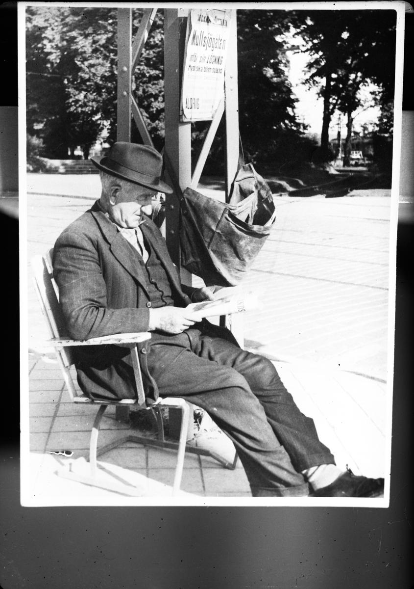 """En tidningsförsäljare läser tidningen Smålands Allahanda bredvid en löpsedel med texten """"Mullsjögåtan inför sin lösning""""."""