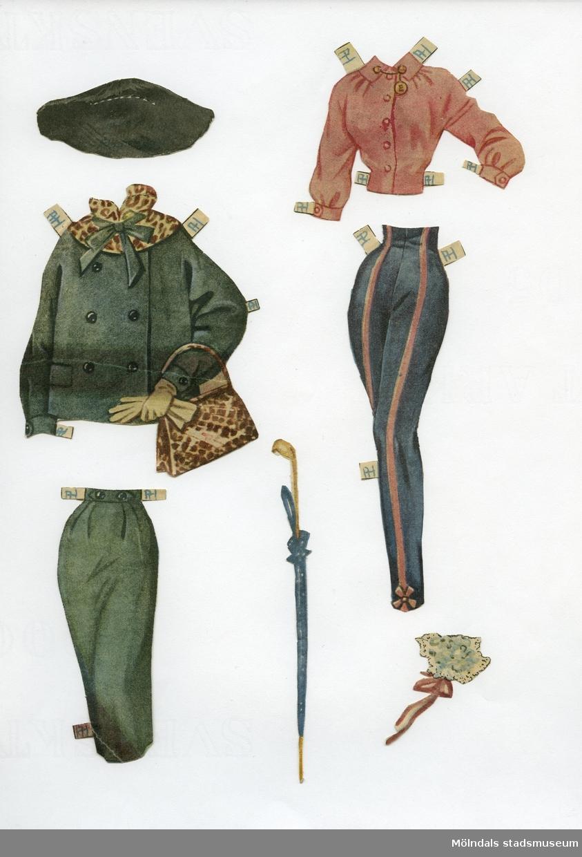 """Klippdocka med kläder och tillbehör från 1950-talet. Docka och kläder märkta """"Audrey Hepburn"""" - dockans namn. Dockan, av papp, föreställer filmstjärnan Audrey Hepburn (1929-1993), tryckt med fotolikhet, och är iklädd underkläder av baddräktsmodell, samt högklackade skor.Dockans garderob, urklippt ur tidning, består av två blusar, två jackor, två kjolar, ett par byxor, tre aftonklänningar, två galaklänningar, samt fem hattar. Dockan har dessutom tillbehör som tre väskor, halsband, scarves, blombukett, paraply, plånbok och väckarklocka. De mindre föremålen har tidigare förvarats tillsammans med klippdockan """"June Allysons"""" småsaker (MM04585) i ett C6-kuvert."""