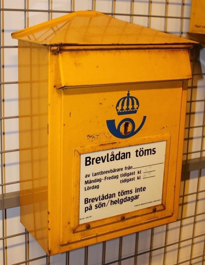 Brevlåda av den modell som ersatte Östbergs modell. Taket är nu inte välvt utan sluttande mot front och gavlar. Fronttömning med anslagsfönster för tömmningstider på tömningslocket. 1965 års postsymbol (den första stiliserade) är placerat så att posthornsslingan omsluter nyckelhålet.