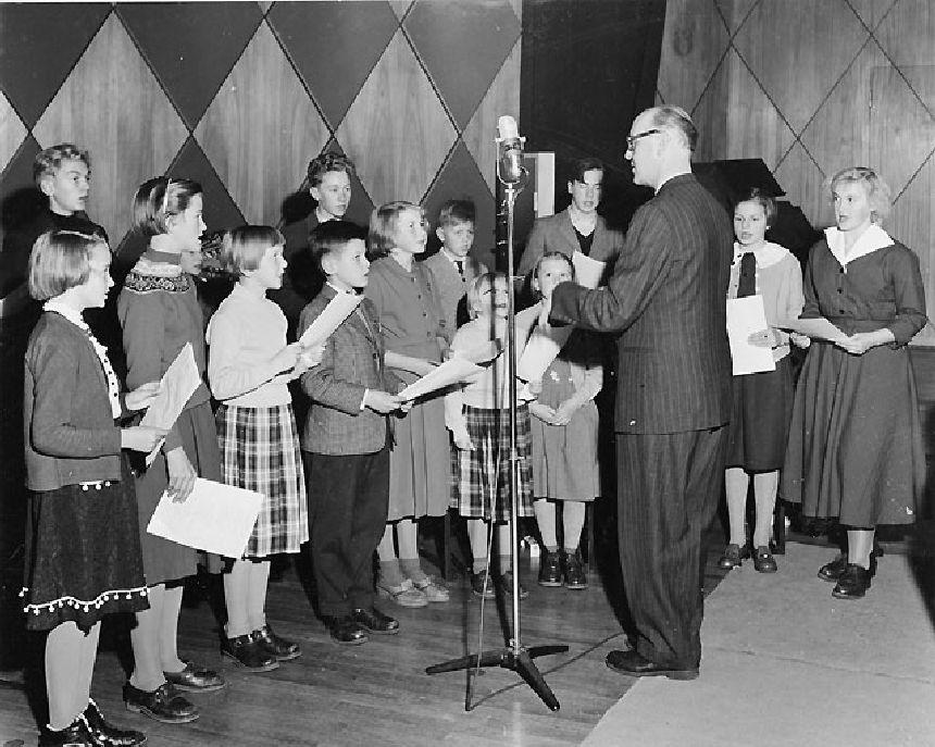 Skolklassen från Holmön sjunger sin egen sparvisa under ledning av sin lärare komminister Sigfrid Landin.