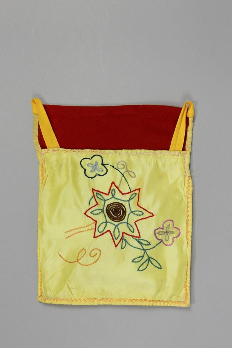 Kjolväska till dräkt för kvinna . Av gul konstsidentaft, med broderi i kedjesöm med konstsilkegarn i flera färger.  Samma typ av broderi på baksidan, samma material. Fodrad med vitt bomullstyg, lakansväv. Överstycke av mjukt rött ylletyg. Kantad längs botten och sidorna med gult konstsidenband. Midjeband gul bomull