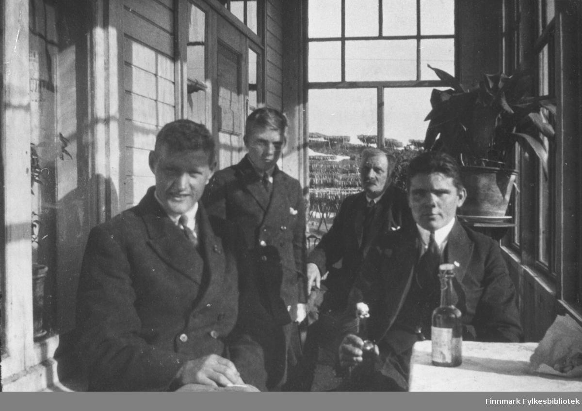 Fire menn er fotografert inne i glassverandaen ca. 1926 Fra v. Evald Hoel, Trygg, Sevaldders og baker Batskin. Batskin var russer, og fungertre som baker i vårsesongene i Kongsfjord. Ellers var han ansatt som baker hos Ottar Frantzen I Berlevåg. (Frantzen var far til Erling Guyldbrandsens kone Alma). På bordet står det brusflasker. Gjennom glassruten i bakgrunnen ser vi fisk som henger på hjell. I et hjørne står en stor grønn plante. Bildetekst i albumet; 'Da Harald var butikkbetjent og Batskin baker. Far og yngste sønn er også med'