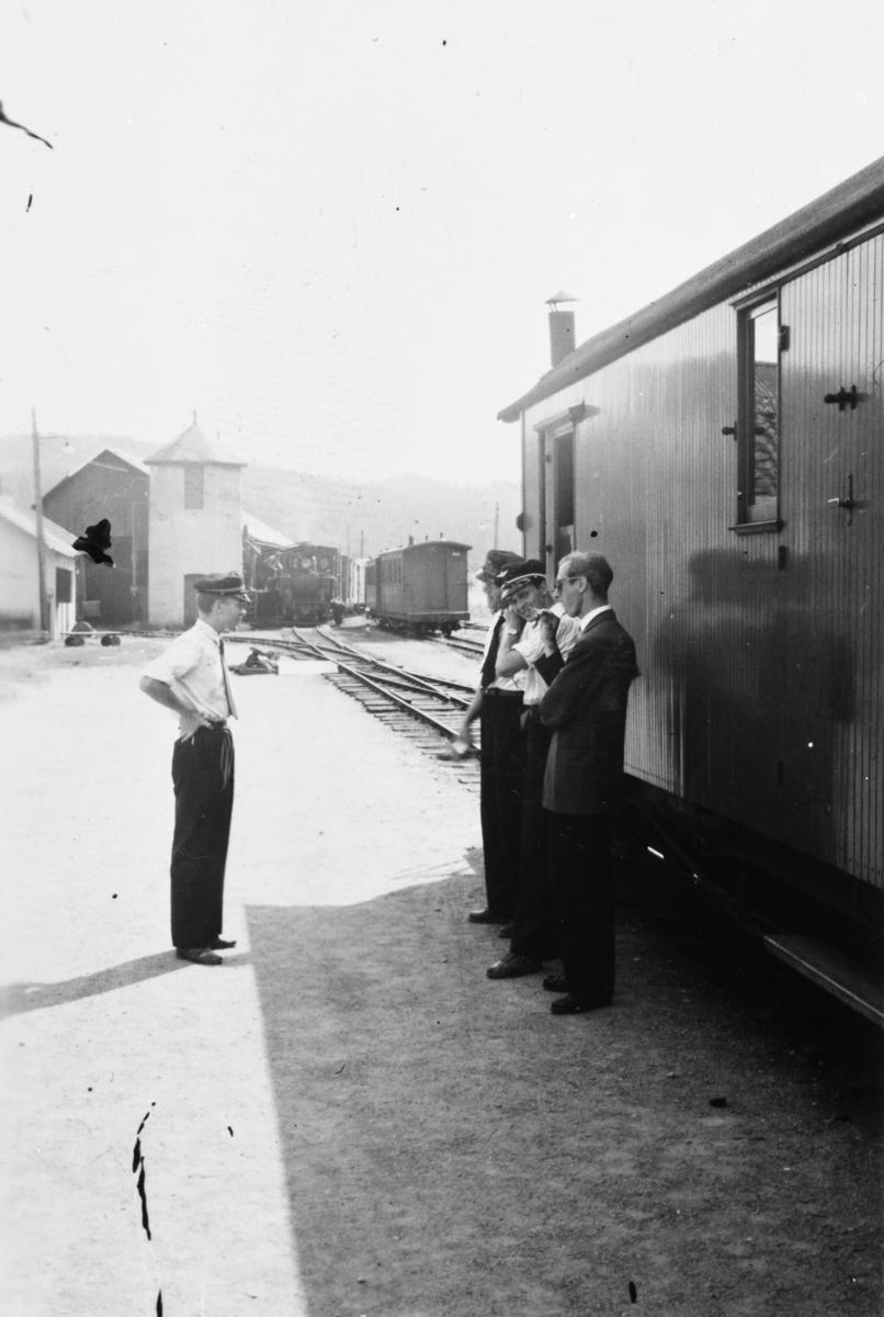 Stasjons- og togpersonale på plattformen under togets opphold på Bjørkelangen stasjon. Lokomotivet har gått rundt toget for å fylle vann fra søndre vanntårn.
