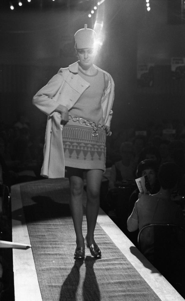 Modevisning, Görtz motor (Rep av oil) 6 april 1967En fotomodell går på catwalken under en modevisning. Hon är klädd i en vit knappa. Den är uppknäppt och under den har hon en ärmlös lårkort klänning med ett metallskärp i midjan. Hon har en ljus hatt på huvudet samt silverskimrande skor. Publik sitter nedanför scenen och tittar på.