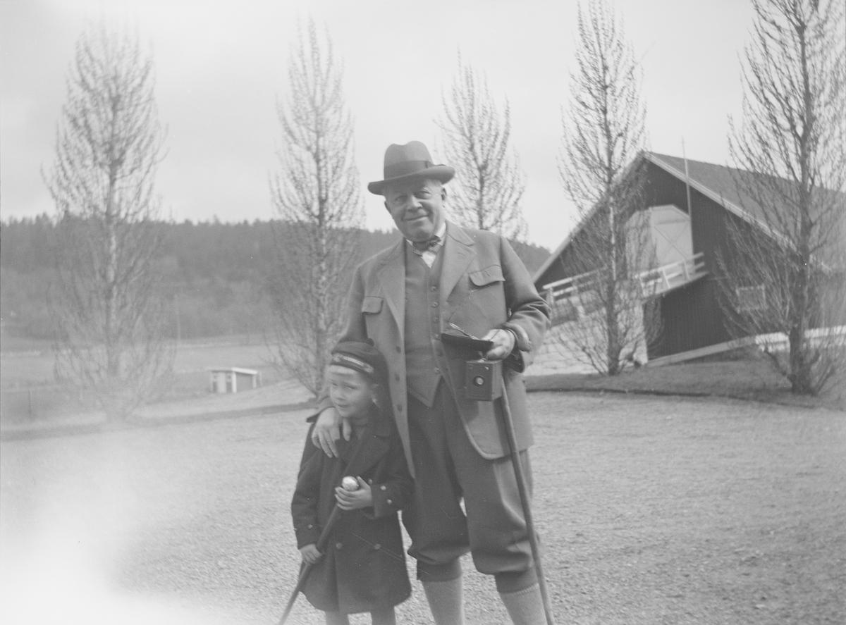 Christian Pierre Mathiesen og et barn står sammen på gårdsplassen på Linderud Gård. Mannen har lagt hånden sin på barnets skulder. Begge ser mot fortografen og smiler. I bakgrunnen sees store løvtrær uten blader og låve med låvebru.