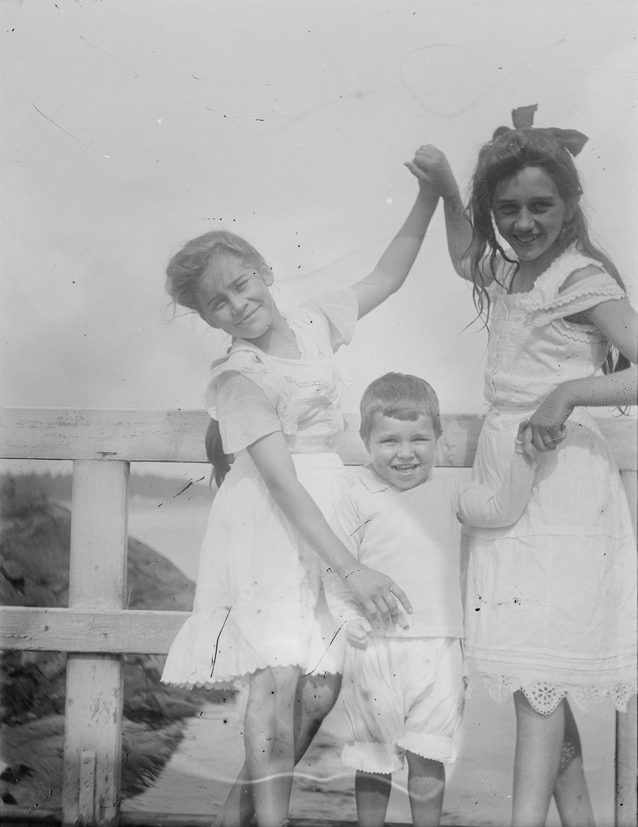 Celina Marie, en gutt og en større jente står på en bro eller en veranda og holder hverandre i hendene. Alle smiler mot fotografen.