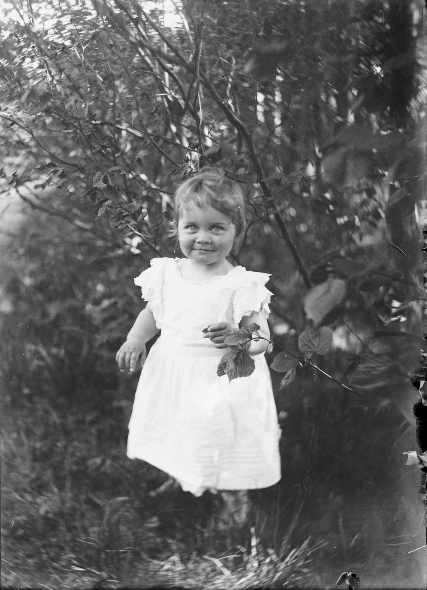 Et barn i står i gresset, ved busker og trær, og smiler til fotografen.