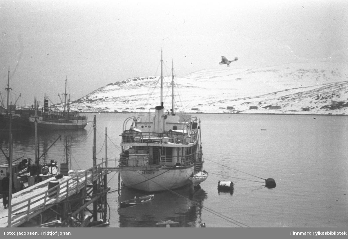 Hospitalskipet Elieser 4 utenfor Dampskipskaia i Hammerfest. En fraktebåt ligger ved kai og skorsteinen på det som sannsyligvis er Hurtigruta ses til venstre på bildet. Noen brakker er kommet opp på Fuglenes. De snødekte fjellene på bildet er Vardfjell til venstre og Storfjellet til høyre. Foten av Fuglenesfjell ses helt til høyre på bildet. Sjøen på bildet er blikkstille. I bakgrunnen lander et Catalinafly.