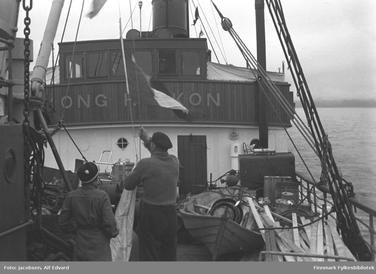 Ombord på D/S Kong Haakon. To personer med ryggen til kamera er i ferd med å heise et flagg. Mannen til venstre på bildet har en forholdsvis lys kjeledress på seg og mørk topplue med en lys stripe og lys dusk. Mannen til høyre, som heiser flagget, har en mørk bukse, litt lysere ullgenser på seg og en mørk skyggelue på hodet. Øverste del av styrhuset har mørkt panel og vinduene øverst står tett i tett. Navnet på skipet står med store blokkbokstaver på veggen under vinduene. En stor og mørk skorstein står på toppen av styrhuset og endel tauverk ses også, noen med vimpler. Topplanterna står helt foran på styrhustaket. Nedre halvdel av styrhuset er hvitt og en mørk dør står omtrent midt på veggen. Et ko-øye ses på veggen til venstre for døra og et dekkslys til høyre. På dekk ligger mye saker. Helt til høyre på bildet ligger en stabel materialer og ved siden av en spissbåt. Til venstre på bildet ses en liten del av formasta med bommen delvis oppe. Tauverk og kjetting ses i forbindelse den. Trommelen og vinsja ses såvidt mellom de to mennene. En taustige er festet i rekka på babord side og går opp mot masta. Flere tau med en talje øverst ses også på samme side. Til høyre på bildet ses den ganske vindstille sjøen og et landparti ses noe diffust i bakgrunnen.