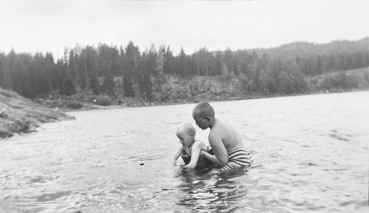 En eldre gutt hjelper en yngre gutt med svømmetrening i en innsjø på østlandet, muligens i Jeppedalen. Den yngste gutten har på svømmebelte.