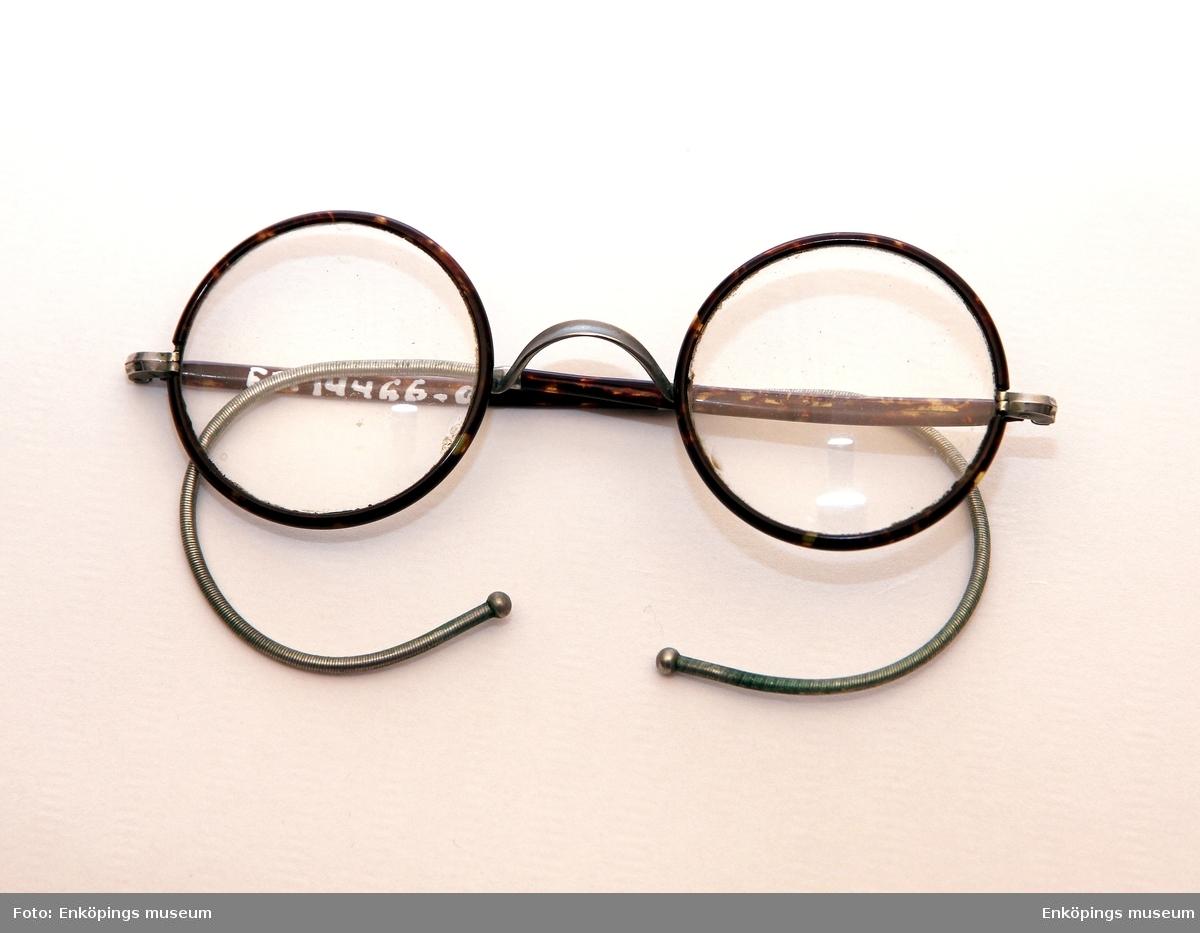 Runda glasögon med metallbågar.