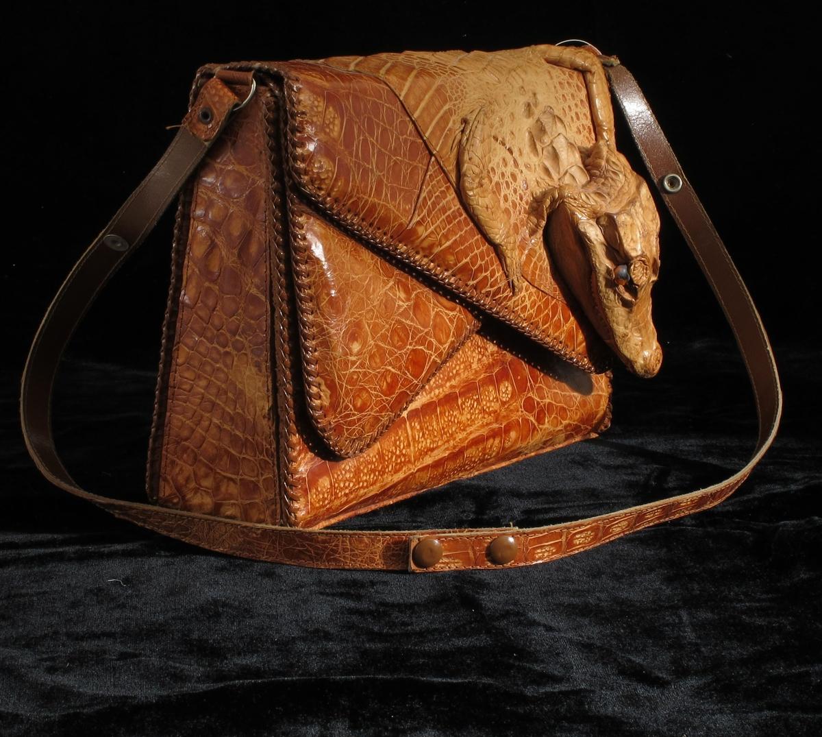 Veske laget av alligatorskinn - hele skinnet et brukt med hode og føtter. Vesken har flere rom og en liten lomme med glidelås.