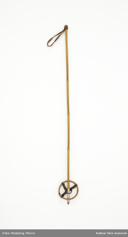 KLM 45702. Skidstav, barnskidstav, 1 st. Av bambu med metallspets och aluminiumskodd nederdel. Kringla med bambugren och läderremmar som hålls fast av metallring fäst i aluminiumskoningen.